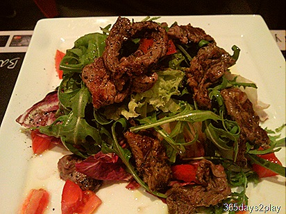 Sliced beef on rocket salad bed